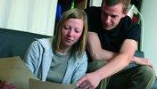 Junge Frauen und junger Mann sehen sich Unterlagen an