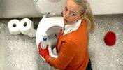 Junge Frau in Bürokleidung putzt Klo