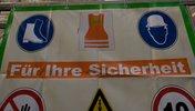 """Schild mit Schutzkleidung und Slogan: """"Für ihre Sicherheit"""""""