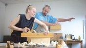 Ein Auszubildende arbeitet an einem Holzhobel und ihr Ausbilder erklärt ihr etwas dazu.