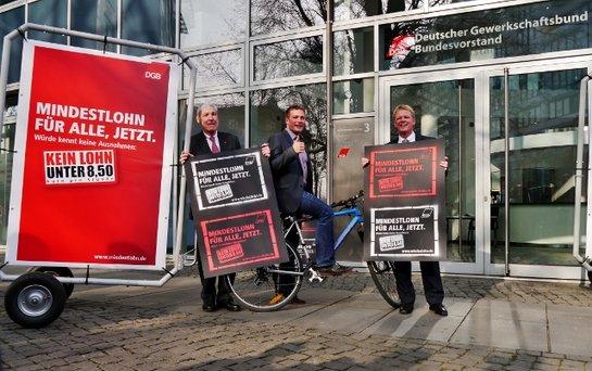 Drei Herren mit dem Mindestlohn Plakat