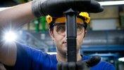 Arbeiter hält eine große Schraube in die Kamera