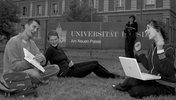 Drei Studierende sitzen auf einer Wiese vor einem Universitätsgebäude und sprechen miteinander.