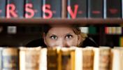 Frau schaut zwischen Büchern eines Bibliotheksregals durch