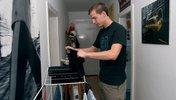 Junger Mann hängt Wäsche auf einen Wäscheständer