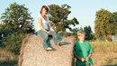 Jugendlichen sitzen im Sonnenuntergang auf einem Heuballen im Sommer.