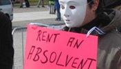 """Demo. Gestalt mit weißer Maske hält Schild: """"Rent an absolvent"""""""