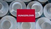 Hungerlohnschild auf leeren Tassen