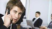 Titelbild des Reports, ein junger Mann am Telefon, im Hintergrund ein Arbeitsraum