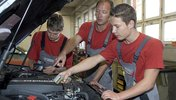 Ausbilder und Auzubildende vor dem Motorraum eines Autos in der Werkstatt