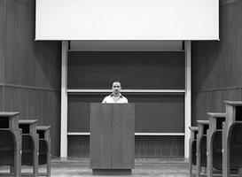 ein Mann steht in einem Hörsaal vor einem Rednerpult