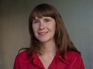 Bild Stefanie Geyer Porträt für mattgrauem Hintergrund. Steffi lächelt freundlich, hat eine rote Bluse an und lange braune Haare