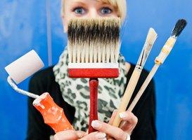 Frau hält Arbeitsmitteln für Maler