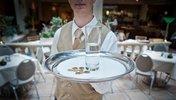 Kellner mit Tablett, auf dem Euromünzen liegen