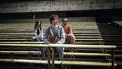 Drei Jugendliche sitzen im Stadion auf der Zuschauertribüne iritierrt schauend