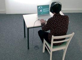 Junger Mann mit Kopfhörern vor einem Computer