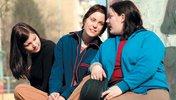 Drei junge Frauen sitzenend miteinander sprechend