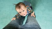 Baby schaut an den Beinen von Erwachsenen hoch