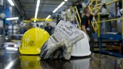 Helme und Sicherheitshandschuhe in der Werkhalle