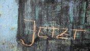 Wort in Kreide auf eine Wand: JETZT