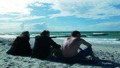 Drei Menschen sitzen am Strand und schauen aufs Meer