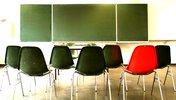 Schwarze und ein roter Stuhl vor einer Tafel