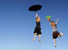 Fliegende Mädchen mit Regenschirm und Bällen